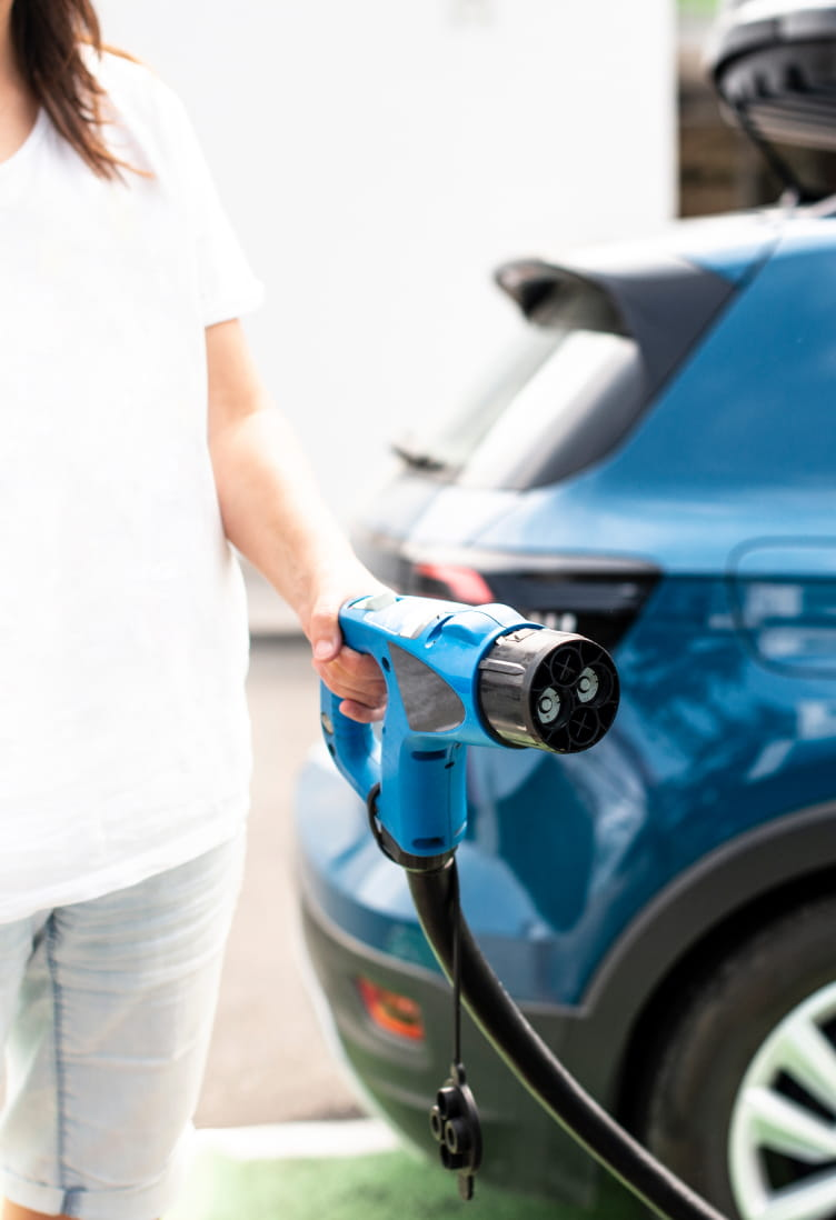 Woman holding a charging cable in front of blue electric car