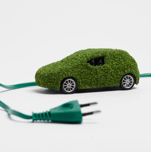 Green, miniature car with a plug